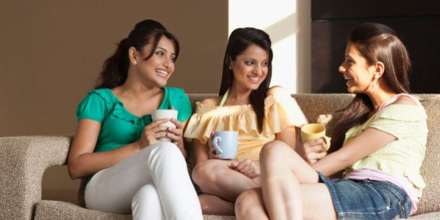 Three young students drinking coffee in living
