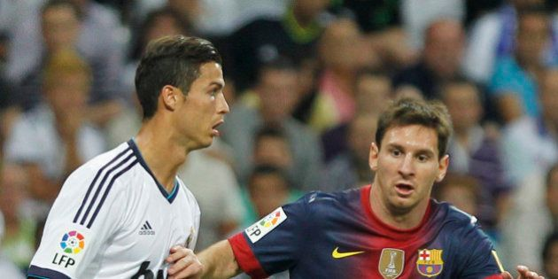 Real Madrid's Cristiano Ronaldo from Portugal, left, vies for the ball with FC Barcelona´s Lionel Messi...