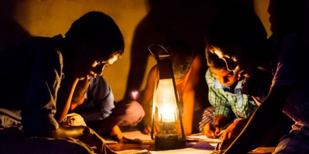 CHOWKIPUR, INDIA, - SEPTEMBER 18: Boys study by lantern light in a house L-R: (children closest to camera)...
