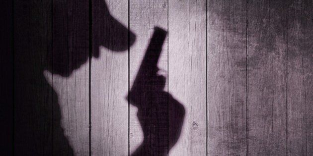 Gangster or investigator or spy silhouette on natural wooden wall. You can see more silhouettes and shadows...