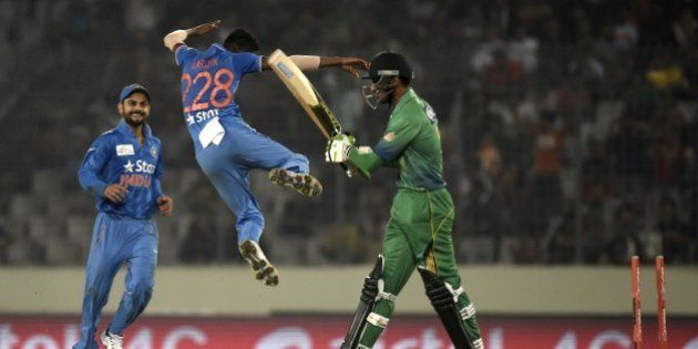 Pakistan cricketer Mohammad Amir (R) walks off the field after being dismissied by Indian cricketer Hardik...