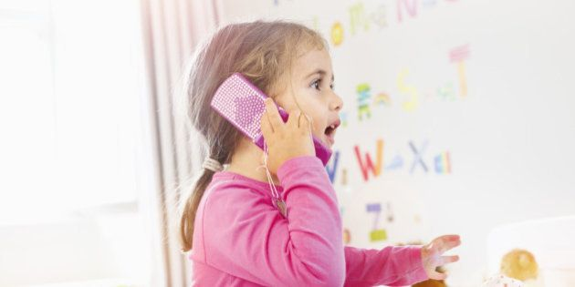young girl is talking on toy mobile