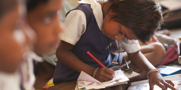Indian schoolgirl studying in the classroom at her poor village school outside Bandhavgarh National Park....