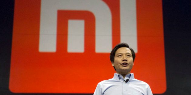 Xiaomi Chairman Lei Jun stands in front of the logo of the Chinese smartphone maker, at a press event...