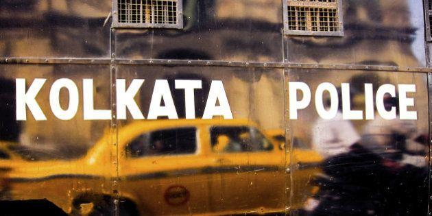 Yellow Ambassador taxi reflecting in black van with Kolkata police inscription. Calcutta,