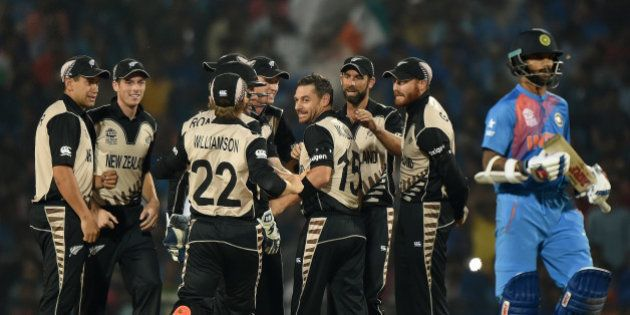 New Zealand bowler Nathan McCullum (4th R) celebrates with team mates after the wicket of India's batsman...