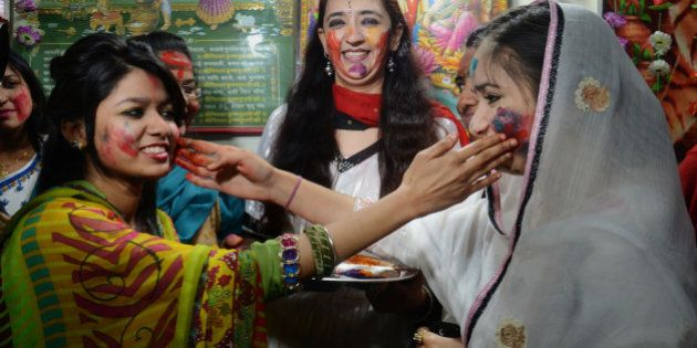 LAHORE, PUNJAB, PAKISTAN - 2015/03/05: Devotees were enjoying wiping colored powders in each other as...