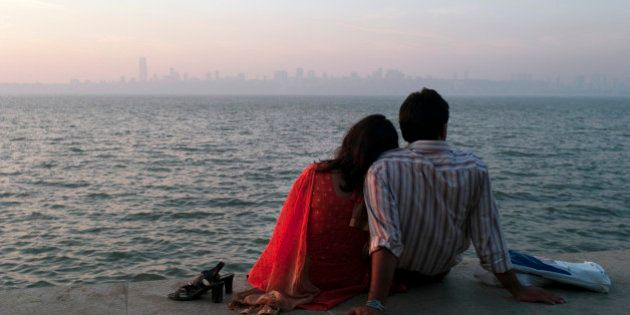 An Indian couple enjoy a sunset view from Marine Drive in Mumbai,