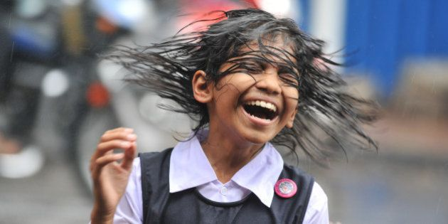 An Indian child shakes her hair during a heavy downpour of rain as she waits for transport outside her...