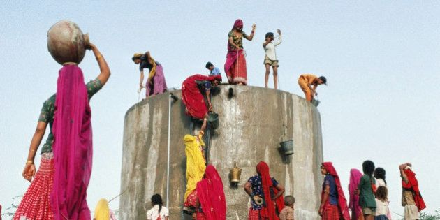 India, Rajasthan,women and children gathering water from concrete