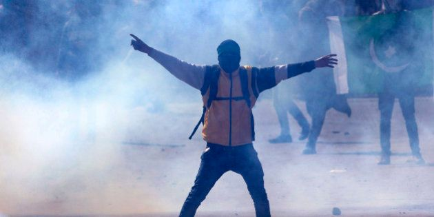 A Kashmiri Muslim protester engulfed in tear gas smoke shouts slogans against India during a protest...