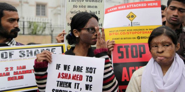 Acid attack victim Laxmi, center, holds placards with others to create awareness during a protest at...