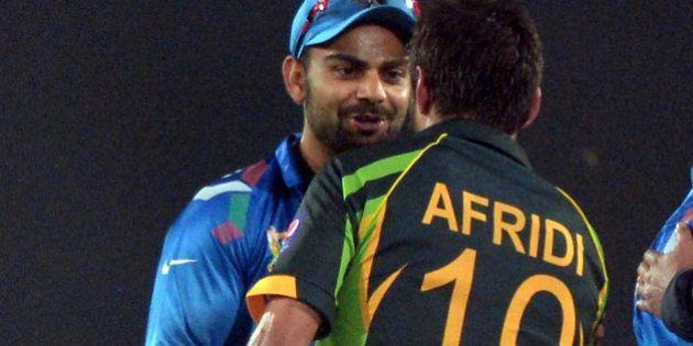 Indian captain Virat Kohli (L) congratulates Pakistani batsman Shahid Afridi for their team's win during...