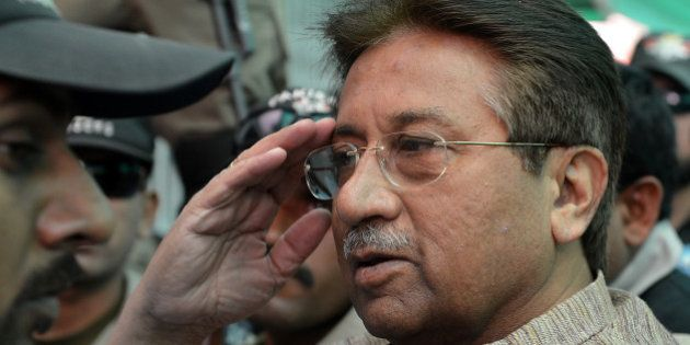 Former Pakistani president Pervez Musharraf (C) is escorted by soldiers as he salutes on his arrival...