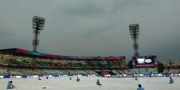 Indian groundstaff sit on tarpaulins over the playing surface as rain falls ahead of the World T20 cricket...