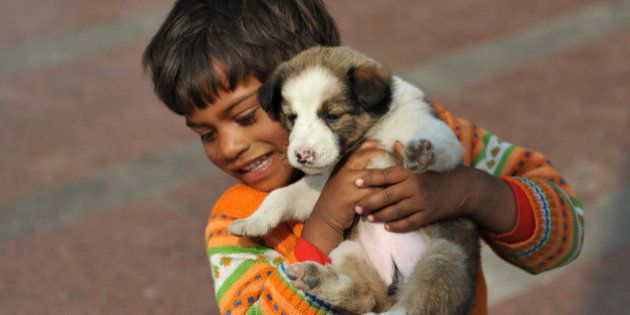 A homeless Indian child plays with a puppy in New Delhi on February 13, 2012. India is home to nearly...