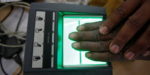 A villager goes through the process of a fingerprint scanner for the Unique Identification (UID) database...