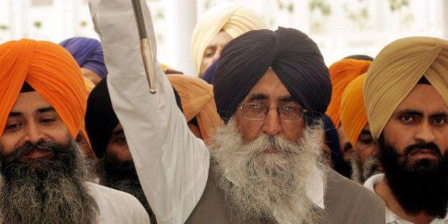 Sikh leader Simranjit Singh Mann, center, raises a sword and shouts religious slogans inside the Golden...