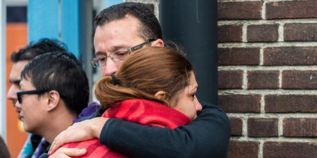 People comfort each other after being evacuated from Brussels airport, after explosions rocked the facility...