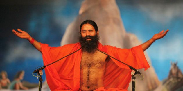 Indian yoga guru Baba Ramdev performs yoga at Sangam, the confluence of rivers Ganges, Yamuna and mythical...
