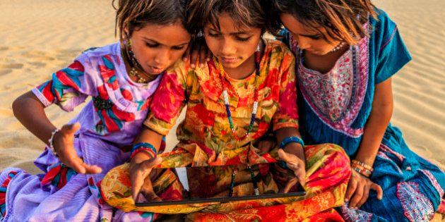 Happy Indian little girls sitting on a sand dune and using tablet in desert village, Thar Desert, Rajasthan,