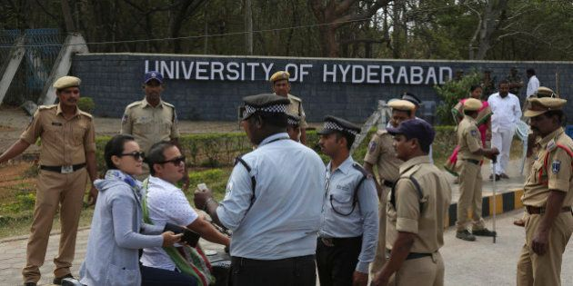 Policemen stand guard as security men check the identity cards of students arriving at the Hyderabad...