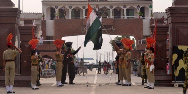 Pakistani Rangers and Indian Border Security Force personnel lower their respective country flags at...