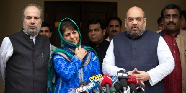 India's ruling Bharatiya Janata Party (BJP) president Amit Shah, right, addresses the media after a meeting...