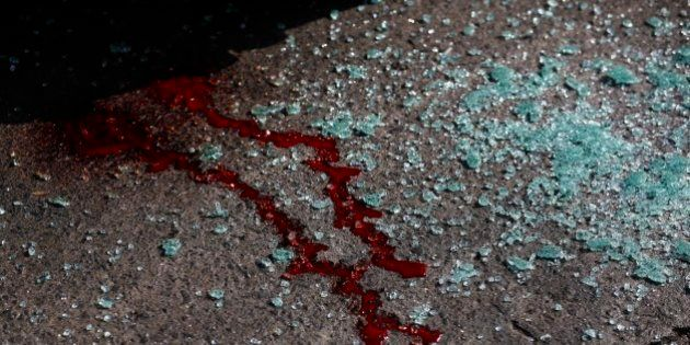 FILE - In this March 3, 2014 file photo, blood and shattered glass cover the pavement after gunmen opened...