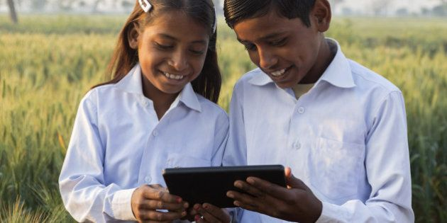 Indian brother and sister wearing school uniform looking at tablet