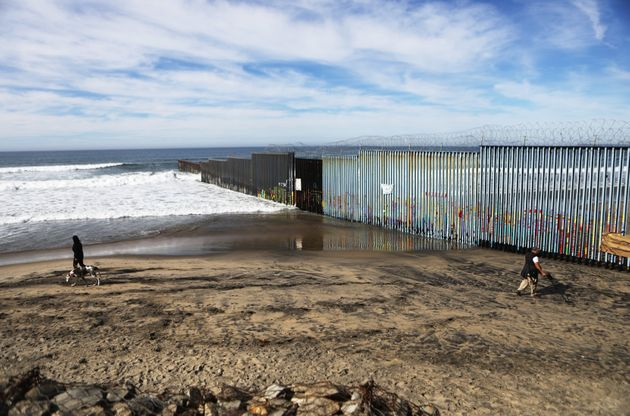 People walk on the Mexican side of the U.S.-Mexico border barrier at the Pacific Ocean on Jan. 8, 2019,...