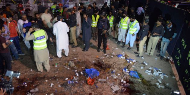 Pakistani rescuers and officials gather at a bomb blast site in Lahore on March 27, 2016.At least 25...