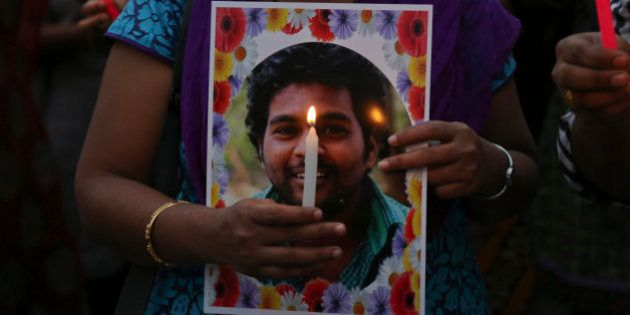 Activist of a Dalit organization participate in a candle light vigil holding photographs of Indian student...