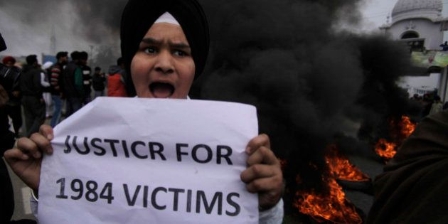 A young Sikh protestor holds a placard as dozens of others burn tires during a protest against Congress...