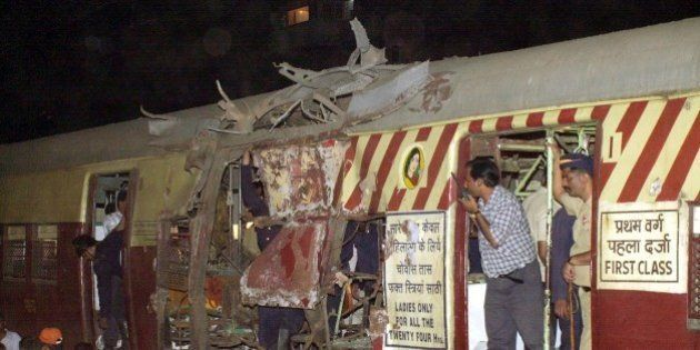 Rescue workers inspect the wreckage of a local train coach at Mulund station in Bombay, India on Thursday,...