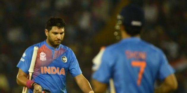 India's Yuvraj Singh(L)reacts as he walks back to the pavilion after his dismissal during the World T20...
