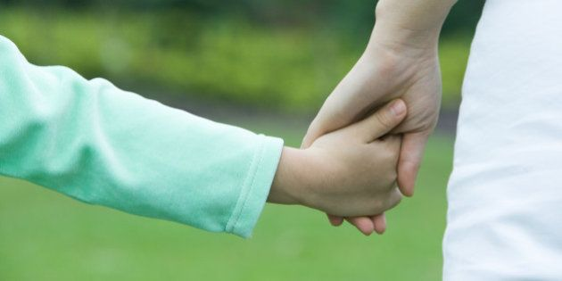 Mother and daughter holding hands, close-up of