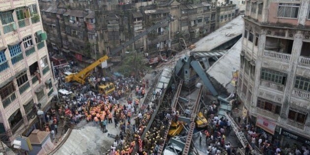 Indian rescue workers and volunteers try to free people trapped under the wreckage of a collapsed fly-over bridge in Kolkata on March 31, 2016.At least 14 people were killed and dozens more injured when a flyover collapsed in a busy Indian city on March 31, an official said, as emergency workers battled to rescue people trapped under the rubble. / AFP / Dibyangshu SARKAR (Photo credit should read DIBYANGSHU SARKAR/AFP/Getty Images)