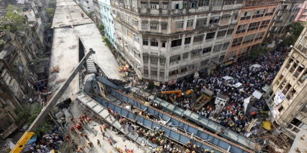 Firefighters and rescue workers search for victims at the site of an under-construction flyover after...