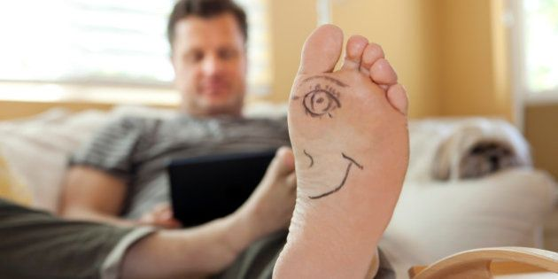 Mans foot with half a face drawn on it using a digital