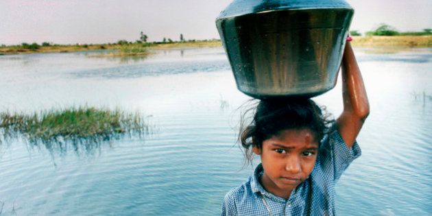 CHENNAI, INDIA, A young Dalit girl draws water from a pond in her village. In the Indian caste system,...