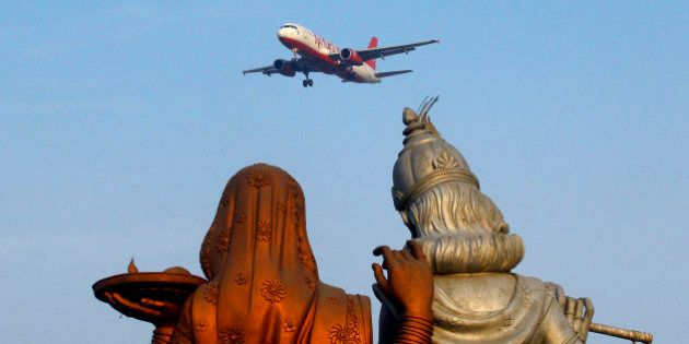 Statue of Hindu Gods Radha, left, and Krishna stand in the foreground as a Kingfisher Airlines flight...