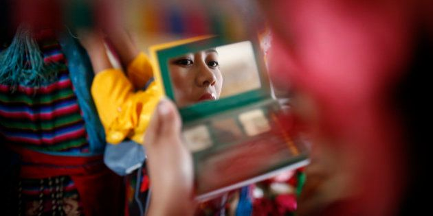 A Tibetan girl in traditional attire looks into the mirror as she prepares ahead of a performance during...