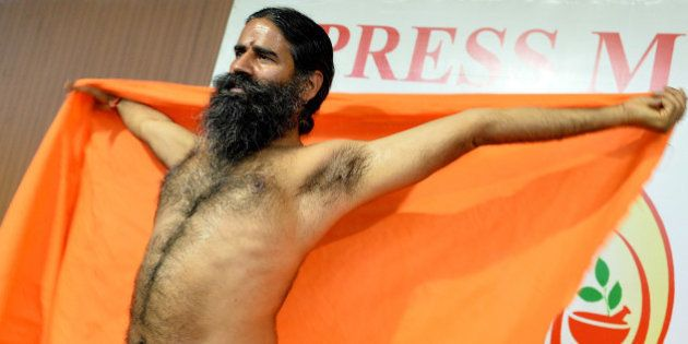 Indian Yoga guru Baba Ramdev stretches after addressing a press conference in Bangalore on March 18,...