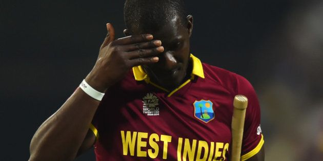 West Indies's captain Darren Sammy gestures as he walks back to the pavilion after his dismissal during...
