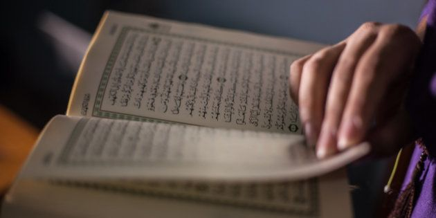 A Muslim woman reads the Quran (Koran).The Quran is the central religious text of Islam, which Muslims...