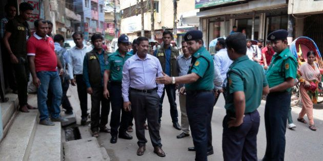 Bangladeshi police officers investigate at the spot where three motorcycle-riding assailants hacked student...
