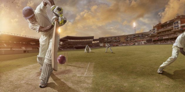 Batsman just after hitting ball in professional cricket match in full stadium at sunset during summer.Stadium...