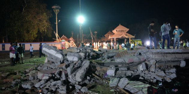 Onlookers and medias stand amidst the debris in the aftermath of the deadly fire explosion that rocked...