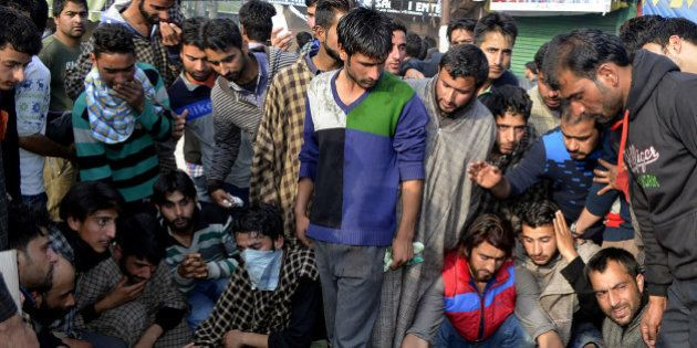 Kashmiri villagers surround the bodies of two civillians reported to have been killed in clashes with...